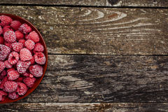Frozen raspberries on wooden background. Top view. Space for text. Royalty Free Stock Photography