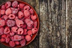 Frozen raspberries on wooden background. Top view. Space for text. Frozen raspberries on the wooden background. Top view. Space for text Stock Image