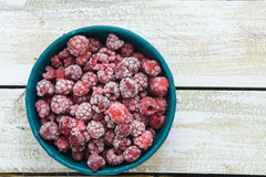 Frozen raspberry berries. Frozen raspberries in a clay bowl on a wooden table stock images