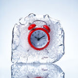Frozen red alarm clock. Red alarm clock in a piece of ice stock photo