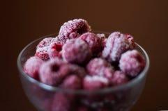 Frozen red berries on dark background. Frozen raspberry in transparent dish stock images