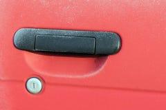 Frozen red car door closeup Stock Photo