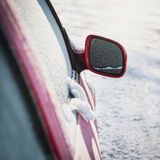 Frozen red car parked outside, with focus on rear view mirror Stock Photos