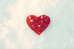 Frozen red heart on snow. Y winter background edited Stock Photo