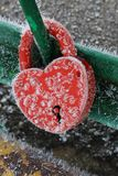 A frozen red metal lock in the shape of a heart Stock Photo