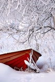 Frozen red rowing boat. Winter has surprised the owner of a red rowing boat. Lots of snow and trees are covered with ice Royalty Free Stock Photography