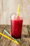 Frozen Red Slushie in Plastic Cup with Straw Stock Images