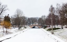 A Frozen Riga Canal in Bastion Hill Park. A winter view along a frozen Riga canal.  The canal flows through Bastion Hill park in Riga, Latvia Royalty Free Stock Photos