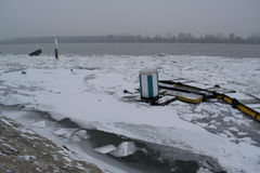 Frozen river with accumulated drift ice putting preasure on dock Royalty Free Stock Photography