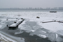 Frozen river with accumulated drift ice putting preasure on dock Stock Photos