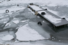 Frozen river with accumulated drift ice putting preasure on dock Stock Photography