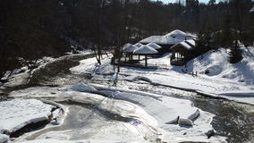 Frozen river bay water wooden houses bank straw roof cover snow stock video