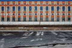 Frozen river and bright orange building. Ice during a thaw in an urban environment. Frozen river and bright orange building. Ice on the channel during the thaw royalty free stock image