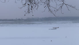 Frozen river Danube in ice and two fishing boats Royalty Free Stock Photo