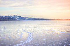 Frozen River and distant mountains stock photos