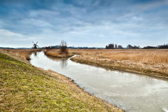 Frozen river and dutch windmill Royalty Free Stock Photos