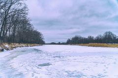 Frozen river and forest in the distance. Winter landscape. Cloudy weather stock images
