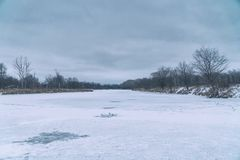 Frozen river and forest in the distance. Winter landscape. Cloudy weather royalty free stock image