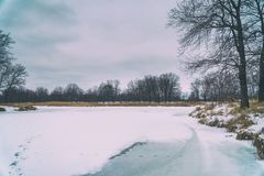 Frozen river and forest in the distance. Winter landscape. Cloudy weather stock image