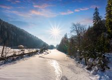 Frozen river in forested mountains. Beautiful scenery with spruce trees and village on the banks Stock Images