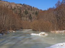 The frozen river at a hill slope Stock Photography