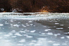 Frozen river with blue ice and sun reflection. Stock Photography
