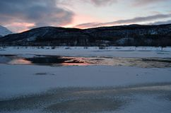 Frozen river landscape with sunny pink glow and reflection. On water stock image