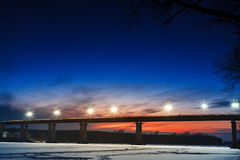 Frozen river with lighted lanterns automobile bridge. Stock Photography