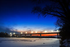 Frozen river with lighted lanterns automobile bridge. Royalty Free Stock Image