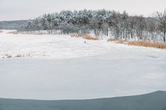 Frozen river in the middle of the forest with a fishermanю royalty free stock photos