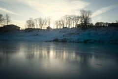 Frozen river shore small town Stock Photos