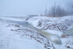 Frozen river and snow meadows in fog Royalty Free Stock Image