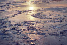 Frozen river water pond reflections texture waves ripple ice sunset sun Stock Images