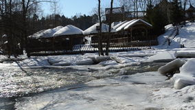 Frozen river water wooden village houses bank roof cover snow stock footage