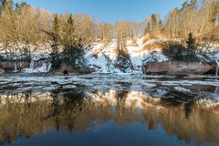 Frozen river in winter. With sandstone cliffs and ice blocks. Gauja National Park. Latvia Stock Photography