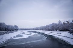 Frozen river, winter in Uzhhorod, Ukraine. View of the snowy embankment of the river with floating ice, snow trees along the coast Stock Image