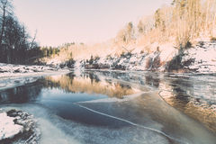 Frozen river in winter -vintage retro effect. Frozen river in winter with sandstone cliffs and ice blocks. Gauja National Park. Latvia. -vintage retro effect Stock Image