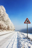 Snow covered road. Snow covered country road with frost and snow covered trees  and sign indicating the approach to a double bend Stock Photography