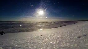 Frozen sea coast:  Snow blizzard during Bright sunny day stock video