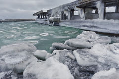 Frozen sea ice,. Ice floes in the beach and the old pier in icicles Royalty Free Stock Image