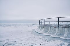 The frozen sea and the iron round pier in ice floes. Ice winter expanse of the sea. Minimalism Stock Photography