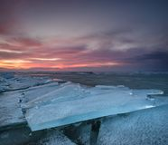 Frozen sea during sunset Stock Photos