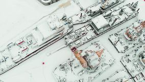 Frozen seaport, winter berths of ships, copter shoot. Frozen seaport, winter berths of ships, ice-bound tankers, simple cranes of the shipyard, aerial view stock footage