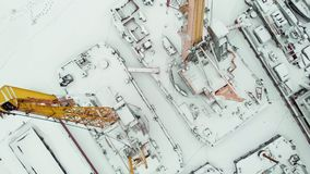 Frozen seaport, winter berths of ships, copter shoot. Frozen seaport, winter berths of ships, ice-bound tankers, simple cranes of the shipyard, aerial view stock video
