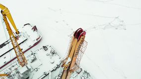 Frozen seaport, winter berths of ships, copter shoot. Frozen seaport, winter berths of ships, ice-bound tankers, simple cranes of the shipyard, aerial view stock video footage