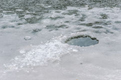 Frozen shards. Fishing hole in the ice when water in the lake is frozen Royalty Free Stock Photography