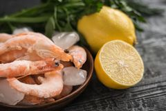 Frozen shrimp with lemon and herbs on clay bowl on black wooden table. Frozen shrimp with lemon and herbs on cutting Board on wooden table. Diet seafood Royalty Free Stock Photos