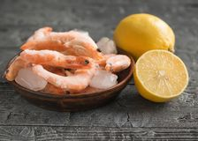 Frozen shrimp with lemon and herbs on clay brown bowl on black wooden rustic table. Frozen shrimp with lemon and herbs on cutting Board on wooden table. Diet Royalty Free Stock Photography