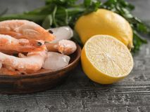 Frozen shrimp with lemon and herbs on clay bowl on black wooden rustic table. Frozen shrimp with lemon and herbs on cutting Board on wooden table. Diet seafood Royalty Free Stock Image