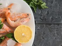 Frozen shrimp with lemon and herbs on white bowl on black wooden rustic table. Top view. Frozen shrimp with lemon and herbs on cutting Board on wooden table Stock Photography